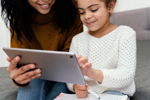 Adolescente ayudando a hermanita con tableta para escuela en línea