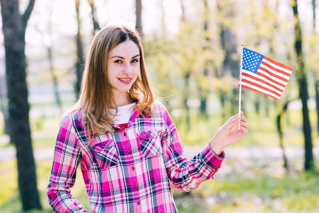 Adolescente con bandera de estados unidos en mano