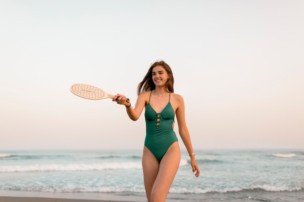 Adolescente en bikini verde jugando con tenis en la orilla del mar