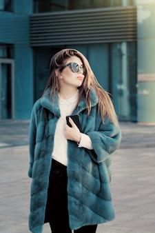Adolescente bonita en un abrigo de piel natural brillante colorido y gafas de sol