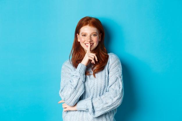 Adolescente bonita pelirroja callando y sonriendo, contando un secreto, de pie en suéter sobre fondo azul.