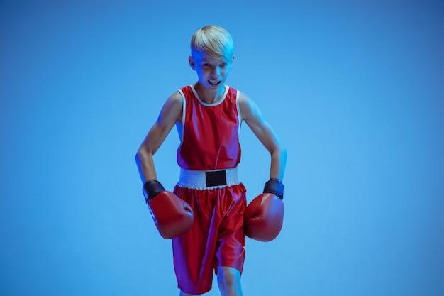 Adolescente en boxeo de ropa deportiva aislado sobre fondo azul de estudio en luz de neón. boxeador caucásico masculino novato entrenando duro y trabajando, pateando. deporte, estilo de vida saludable, concepto de movimiento.