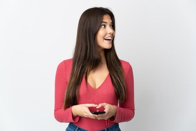 Adolescente brasileña aislada en la pared blanca mediante teléfono móvil y mirando hacia arriba