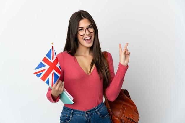 Adolescente brasileña sosteniendo una bandera del reino unido aislado sobre fondo blanco sonriendo y mostrando el signo de la victoria