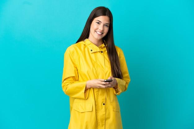 Adolescente brasileña vistiendo un abrigo impermeable sobre fondo azul aislado enviando un mensaje con el móvil