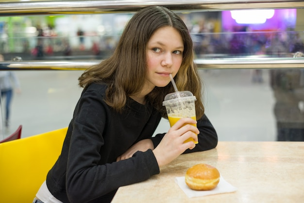 Adolescente en la cafetería comiendo pastel y jugo de naranja