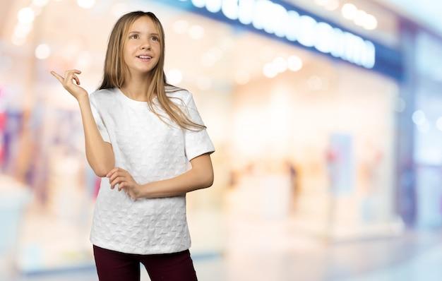 Adolescente en camisa blanca apuntando con su dedo