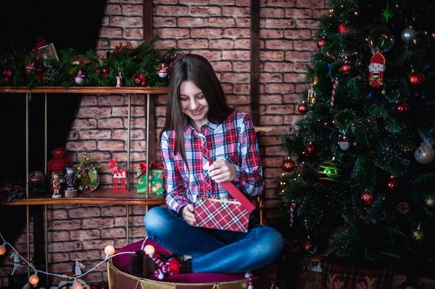 Adolescente en una camisa a cuadros abre caja de regalo de navidad