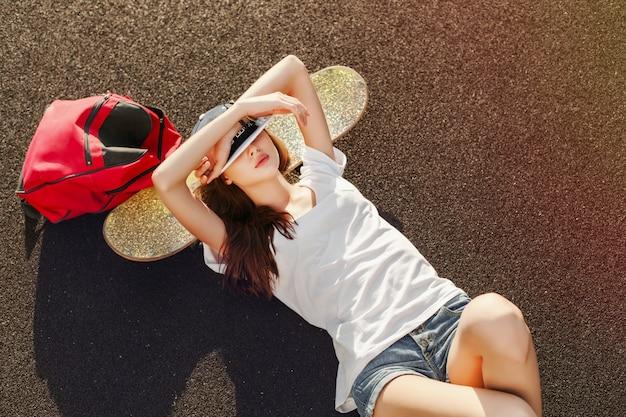 Adolescente con camiseta blanca descansando en el monopatín