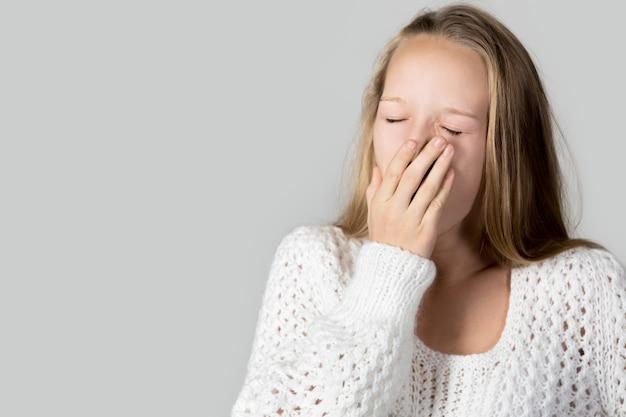Adolescente cansada bostezando
