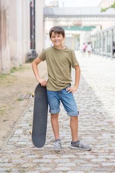 Un adolescente cargando patineta y sonriendo