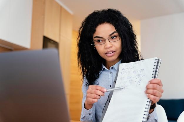 Adolescente en casa durante la escuela en línea con laptop y notebook