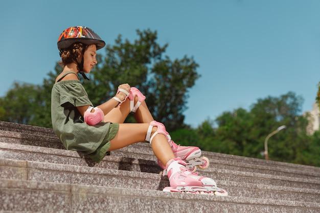 Adolescente en un casco aprende a andar en patines sosteniendo un equilibrio o patinar y girar en la calle de la ciudad en un día soleado de verano