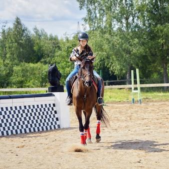 Adolescente con casco está aprendiendo a montar a caballo en el campo de equitación