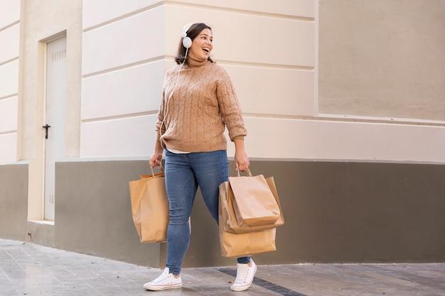 Adolescente casual llevando bolsas de la compra.