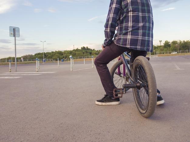 Adolescente casual sentado escalofriante en bicicleta en el gran campo de deportes de asfalto