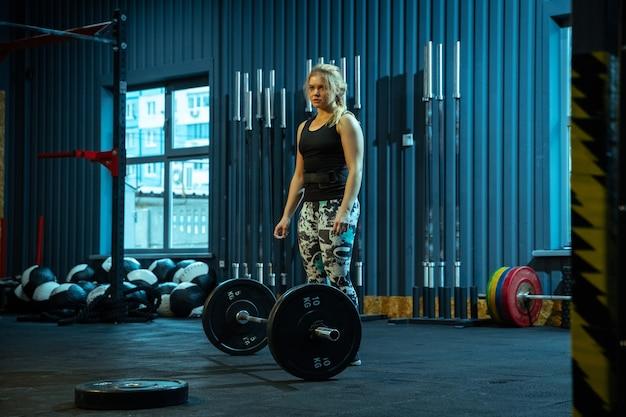 Adolescente caucásica practicando levantamiento de pesas en el gimnasio.
