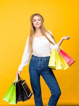 Adolescente caucásica sobre fondo amarillo. mujer joven elegante con bolsas de la compra en las manos - imagen