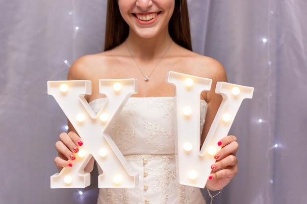 Adolescente celebrando quinceañera mientras sostiene números romanos