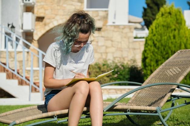Adolescente chica de 15, 16 años sentada en una tumbona en el césped, escribiendo con lápiz en el cuaderno. regreso a clases, inicio de clases en verano