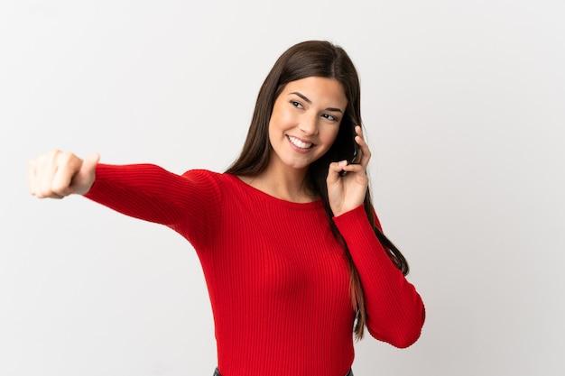 Adolescente chica brasileña a través de teléfono móvil sobre fondo blanco aislado dando un gesto de pulgar hacia arriba