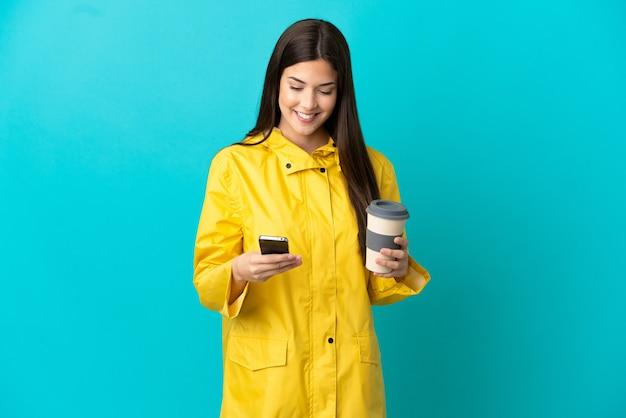 Adolescente chica brasileña vistiendo un abrigo impermeable sobre fondo azul aislado sosteniendo café para llevar y un móvil