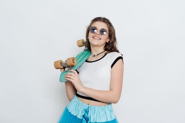 Adolescente chica elegante feliz en gafas de sol posando con tablero de centavo en blanco