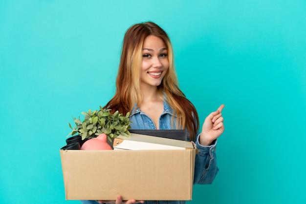 Adolescente chica rubia haciendo un movimiento mientras recoge una caja llena de cosas apuntando hacia atrás