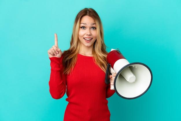 Adolescente chica rubia sobre fondo azul aislado sosteniendo un megáfono y apuntando hacia una gran idea