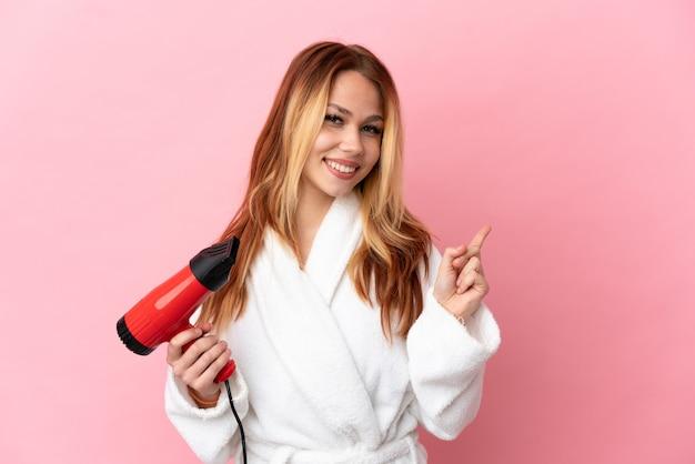 Adolescente chica rubia sosteniendo un secador de pelo sobre fondo rosa aislado apuntando hacia atrás