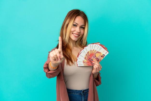 Adolescente chica rubia tomando un montón de euros sobre fondo azul aislado mostrando y levantando un dedo