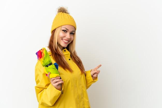 Adolescente chica rubia vistiendo un abrigo impermeable sobre fondo blanco aislado apuntando hacia atrás