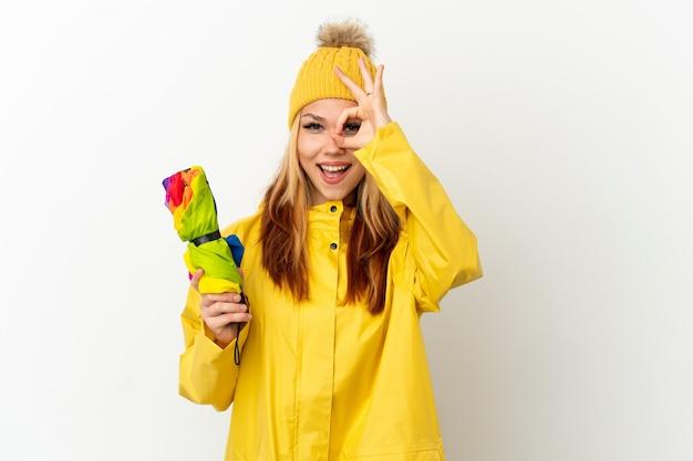 Adolescente chica rubia vistiendo un abrigo impermeable sobre fondo blanco aislado mostrando el signo de ok con los dedos