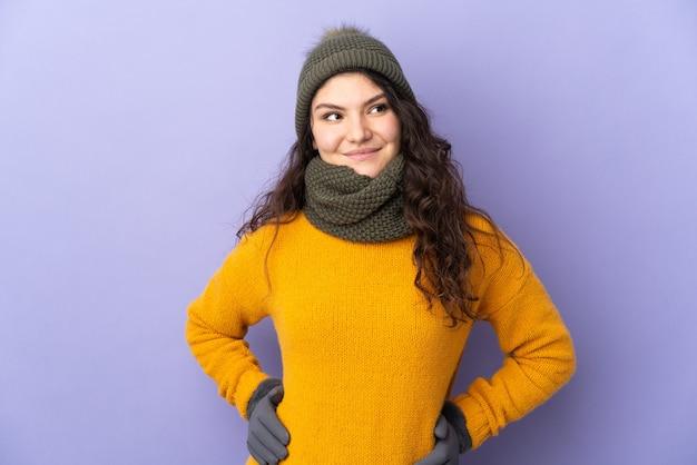 Adolescente chica rusa con sombrero de invierno aislado sobre fondo púrpura posando con los brazos en la cadera y sonriendo