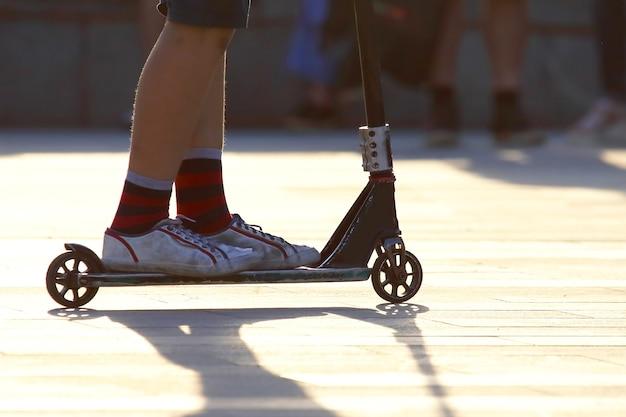 Adolescente en la ciudad en scooter. deportes y pasatiempos. entretenimiento juvenil