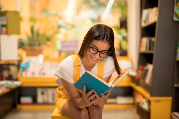 Adolescente colegiala leyendo libro cautivado