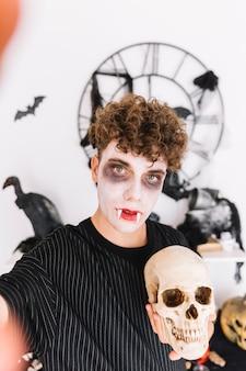 Adolescente con colmillos haciendo selfie con calavera