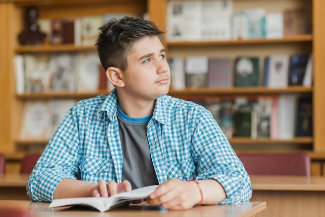 Adolescente con libro mirando a otro lado