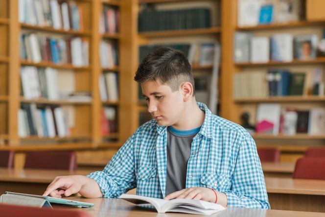 Adolescente con libro usando tableta