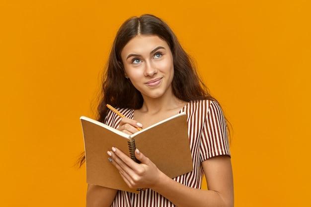 Adolescente creativa vestida con top rayado sosteniendo un diario y mirando hacia arriba