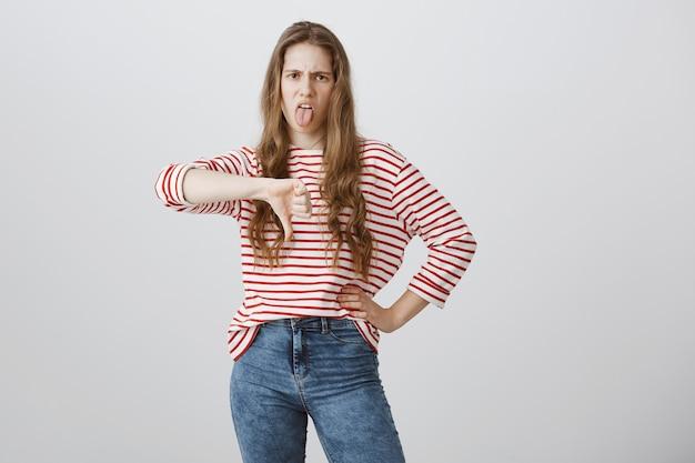 Adolescente decepcionada y molesta, con aspecto escéptico, mostrando la lengua y el pulgar hacia abajo con disgusto