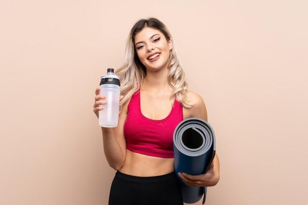 Adolescente deporte chica con botella de agua deportiva y con una estera