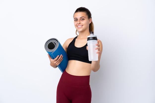 Adolescente deporte mujer sobre pared blanca aislada con botella de agua deportiva y con una estera