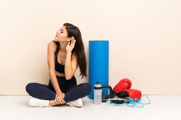 Adolescente deporte niña sentada en el suelo escuchando algo poniendo la mano en la oreja