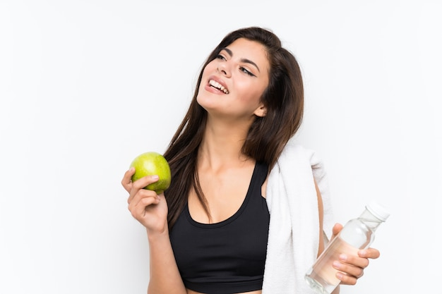 Adolescente deporte niña sobre fondo blanco aislado con una manzana y una botella de agua