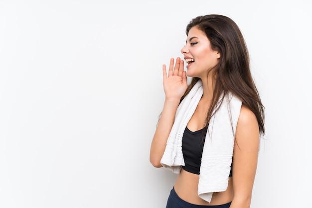 Adolescente deporte niña sobre pared blanca aislada gritando con la boca abierta