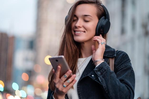 Adolescente disfruta y escucha música en auriculares inalámbricos negros mientras camina por la ciudad