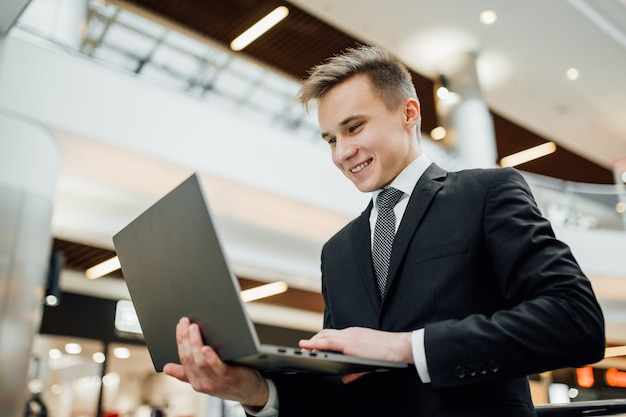 Adolescente se divierte en la computadora portátil, vestido de negro, en el centro comercial, divertido, interior, emociones faciales positivas