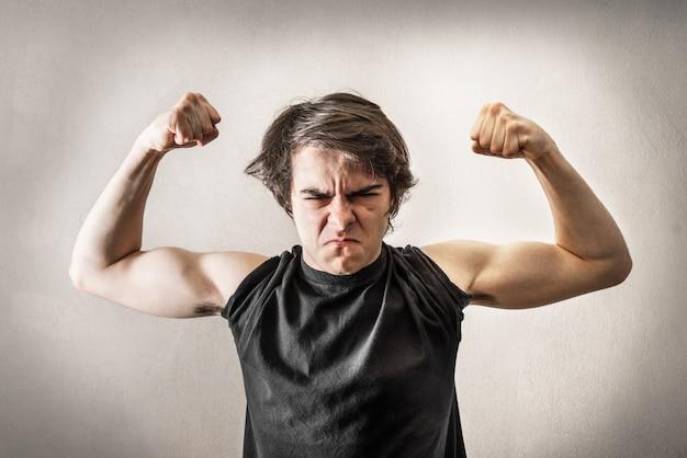 Adolescente enojado mostrando músculos