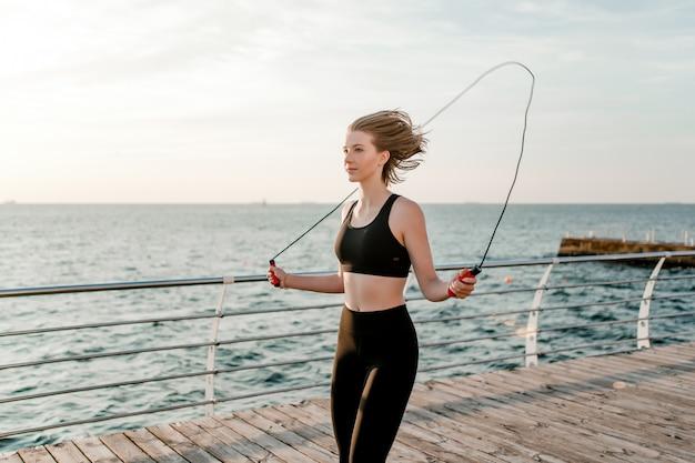 Adolescente entrenando con una comba en la playa